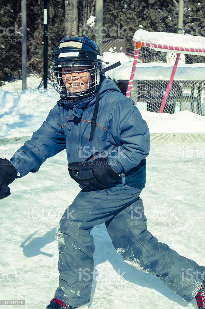 A little boy who is happy ice skating on rink royalty-free stock photo