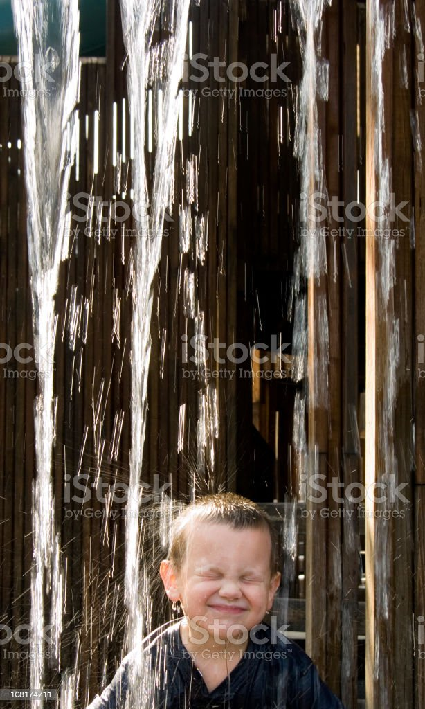 Little Boy Winching and Standing Underneath Falling Water royalty-free stock photo