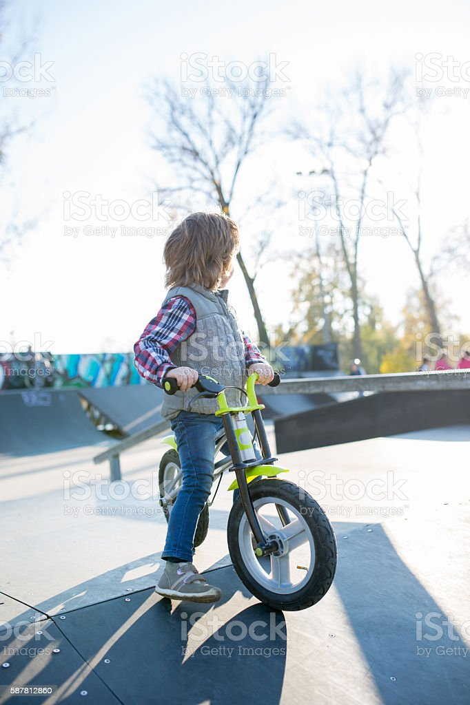 Little boy with a bicycle in skate park. stock photo