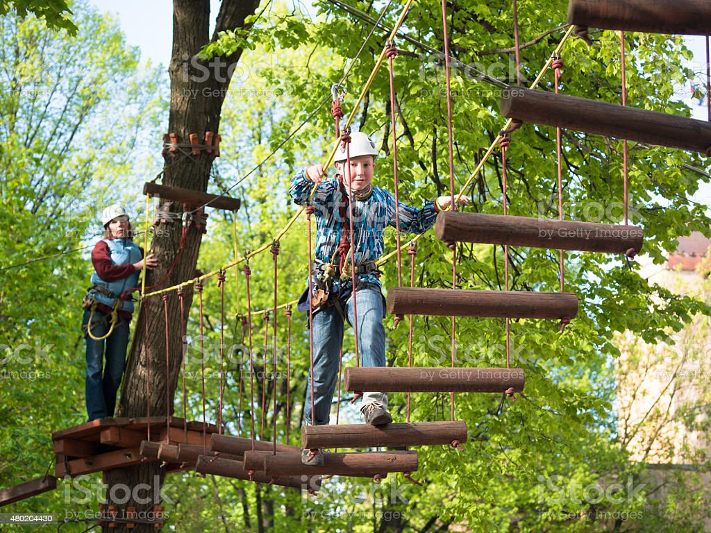 Little boy  with a safety carbine goes on a rope stock photo