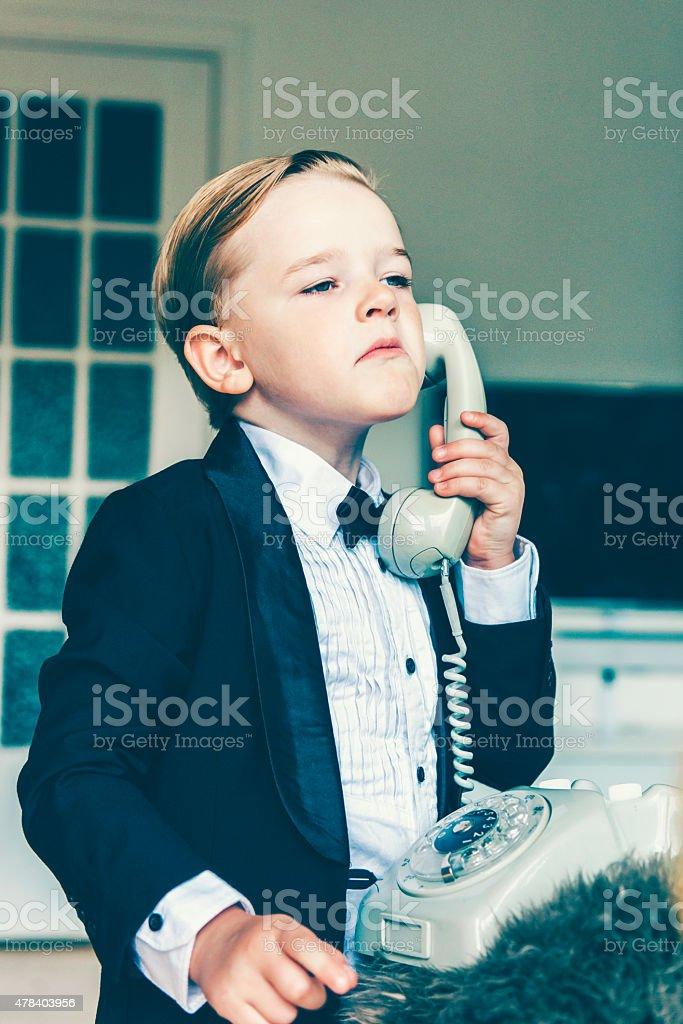 Little boy with an attitude talks on an old telephone stock photo