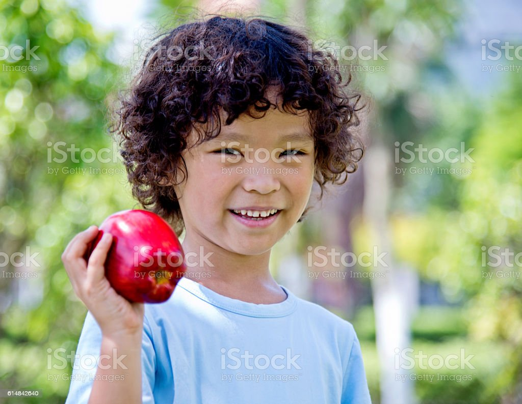 Little boy with apple outdoors stock photo