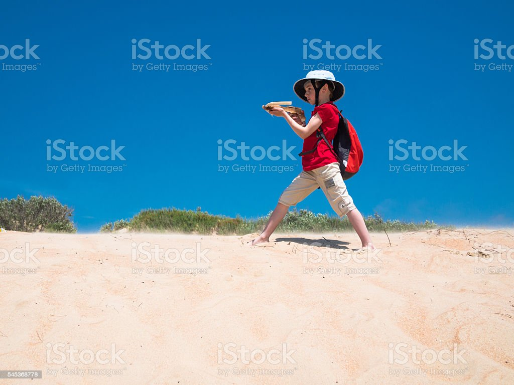Little boy with backpack and a crossbow in his hands stock photo