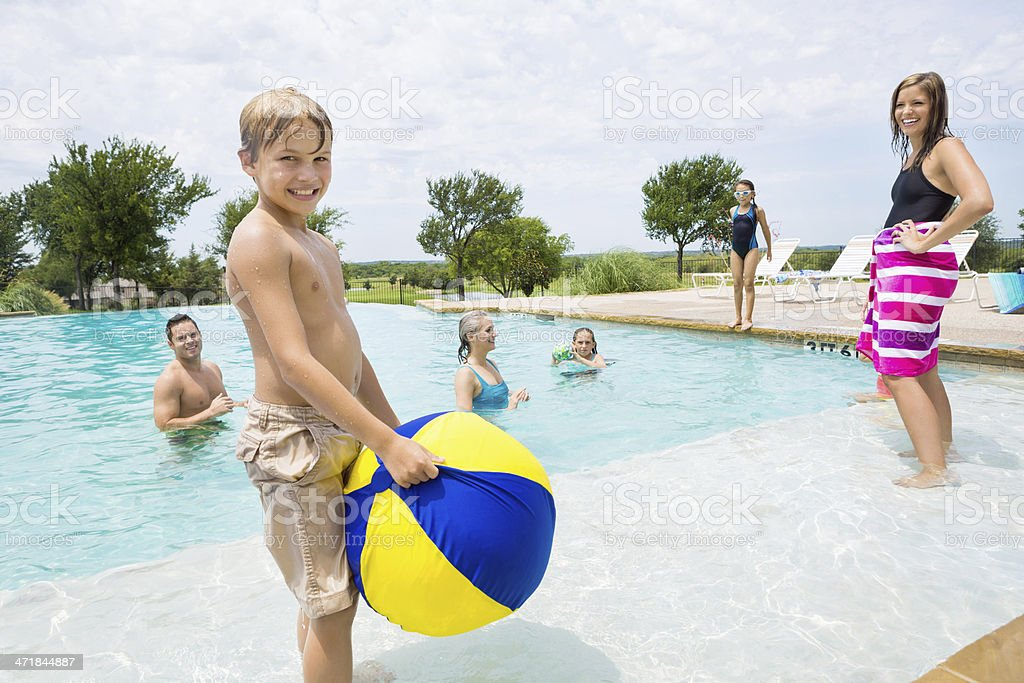 Little boy with beach ball playing at family pool royalty-free stock photo