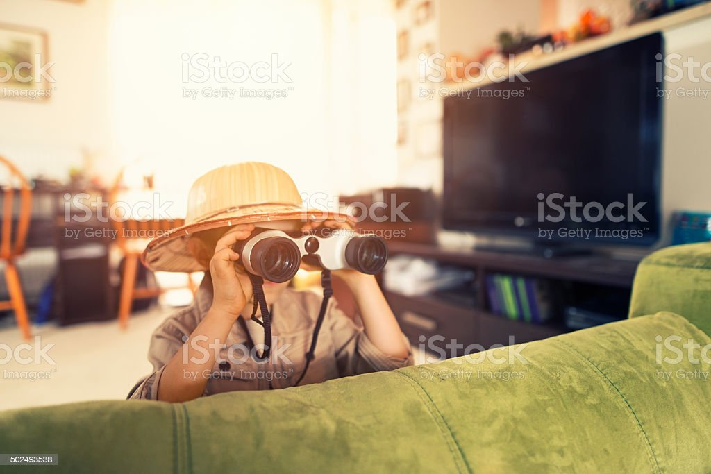 Little boy with binoculars exploring living room stock photo