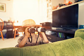 Little boy with binoculars exploring living room