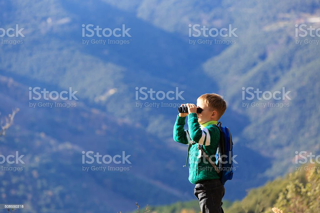 little boy with binoculars hiking in mountains stock photo
