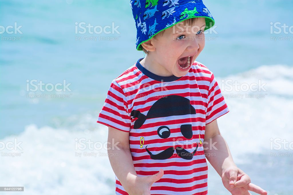 Little boy with blue eyes screaming with happiness stock photo
