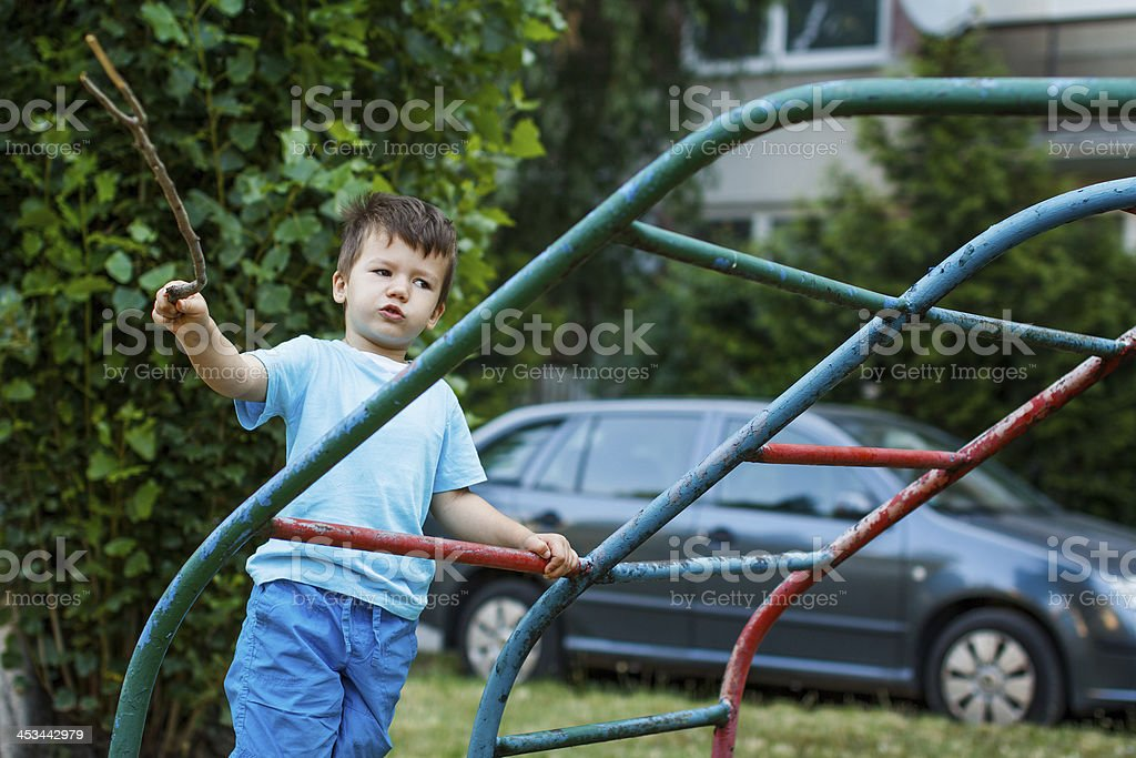 Little boy with branch on jungle gym royalty-free stock photo