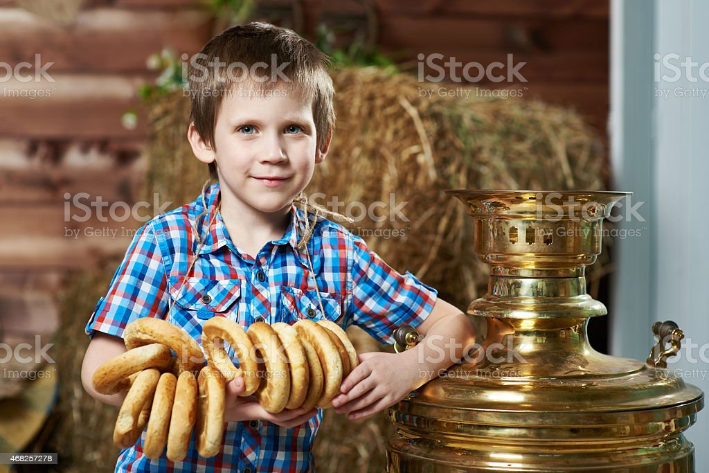 Little boy with bread-rings around large samovar stock photo