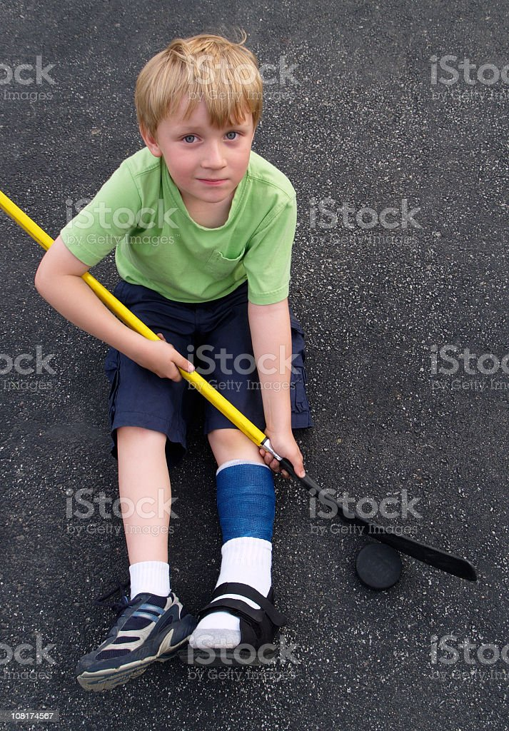 Little Boy With Cast on Leg Playing Street Hockey royalty-free stock photo