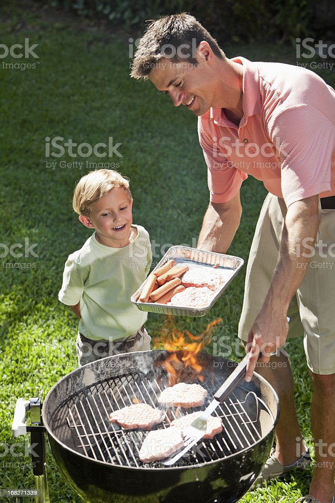 Little boy with dad grilling hotdogs and burgers royalty-free stock photo
