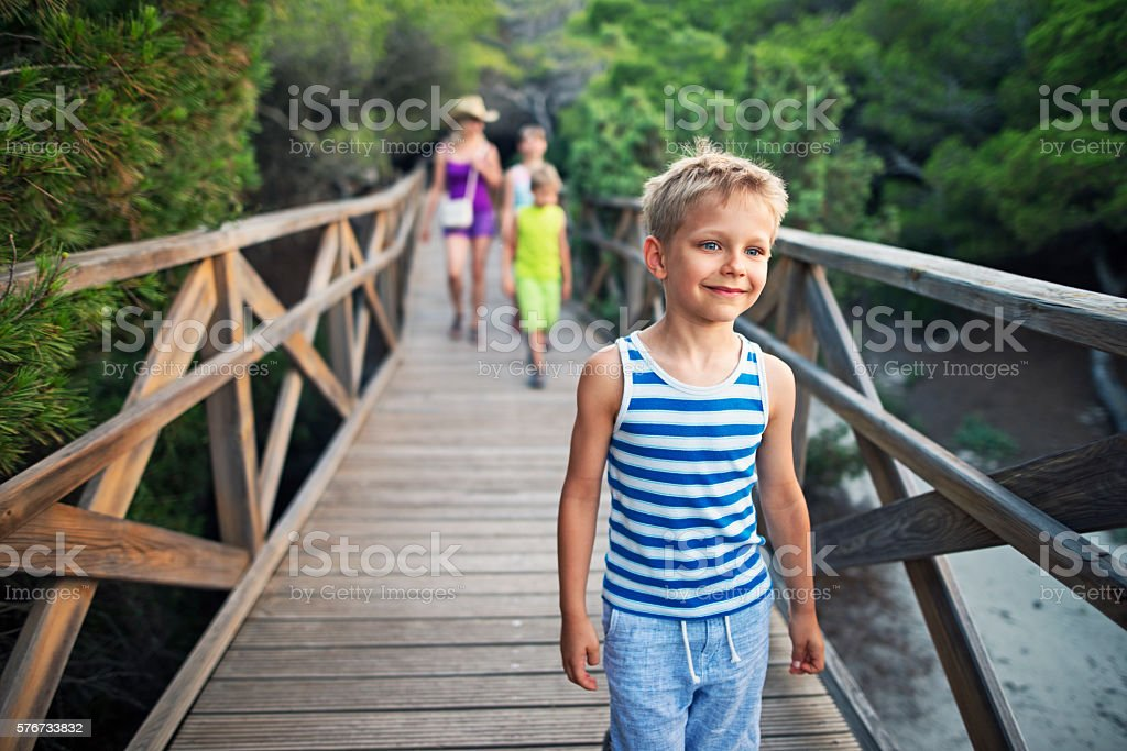 Little boy with family walking on a ramp through forest stock photo
