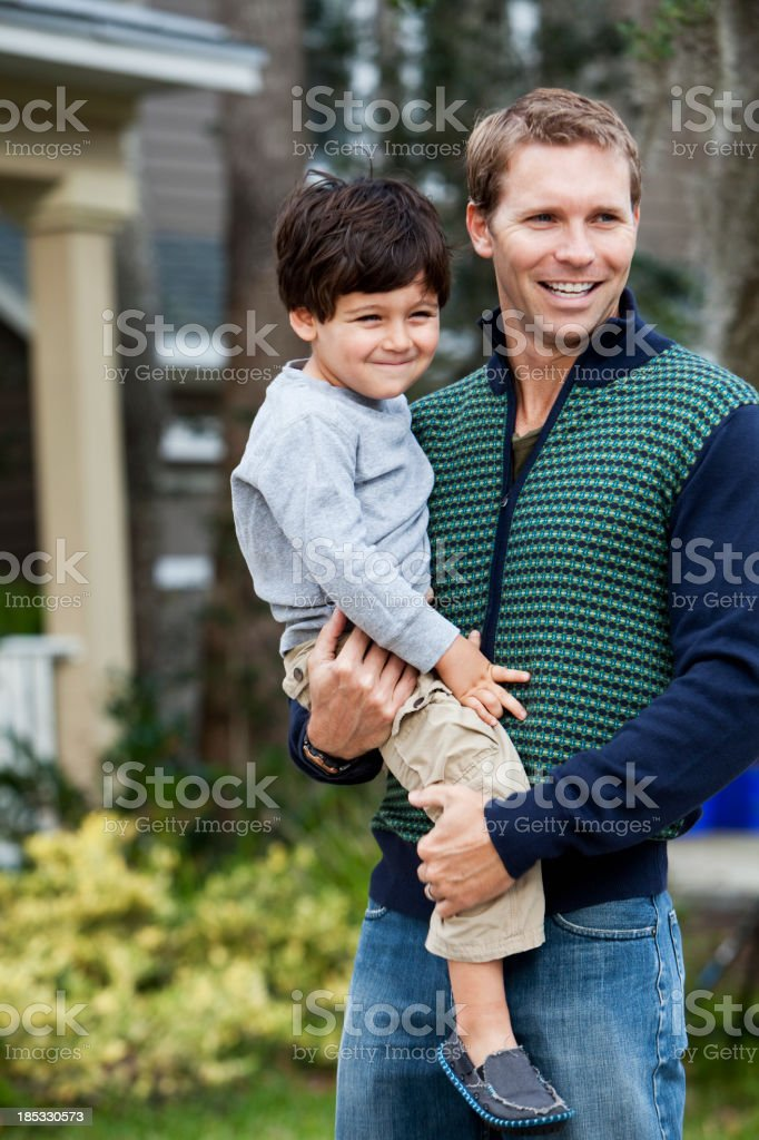 Little boy with father in front of house stock photo
