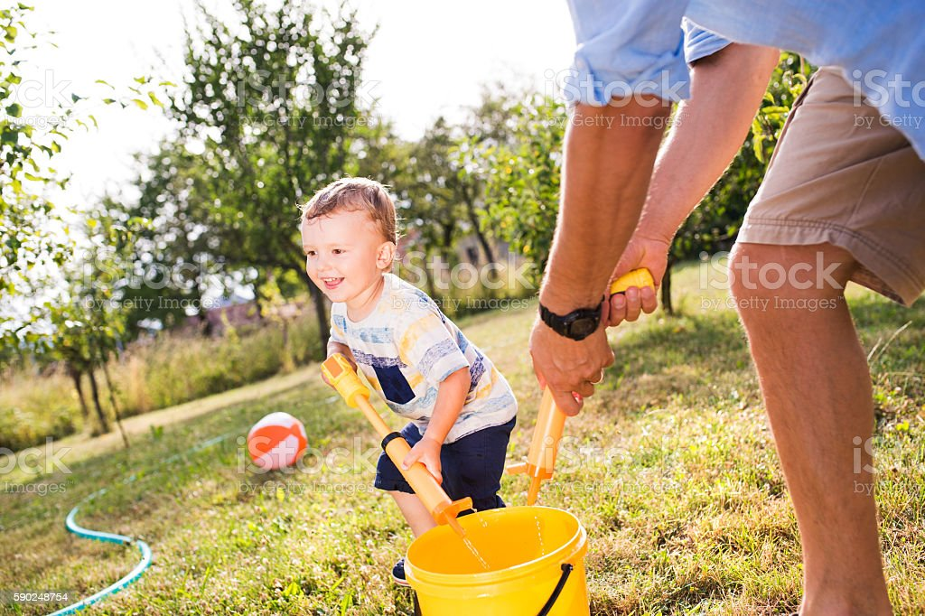 Little boy with father playing with water guns, splashing stock photo