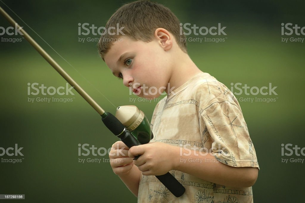 Little boy with fishing rod looking curious and interested royalty-free stock photo