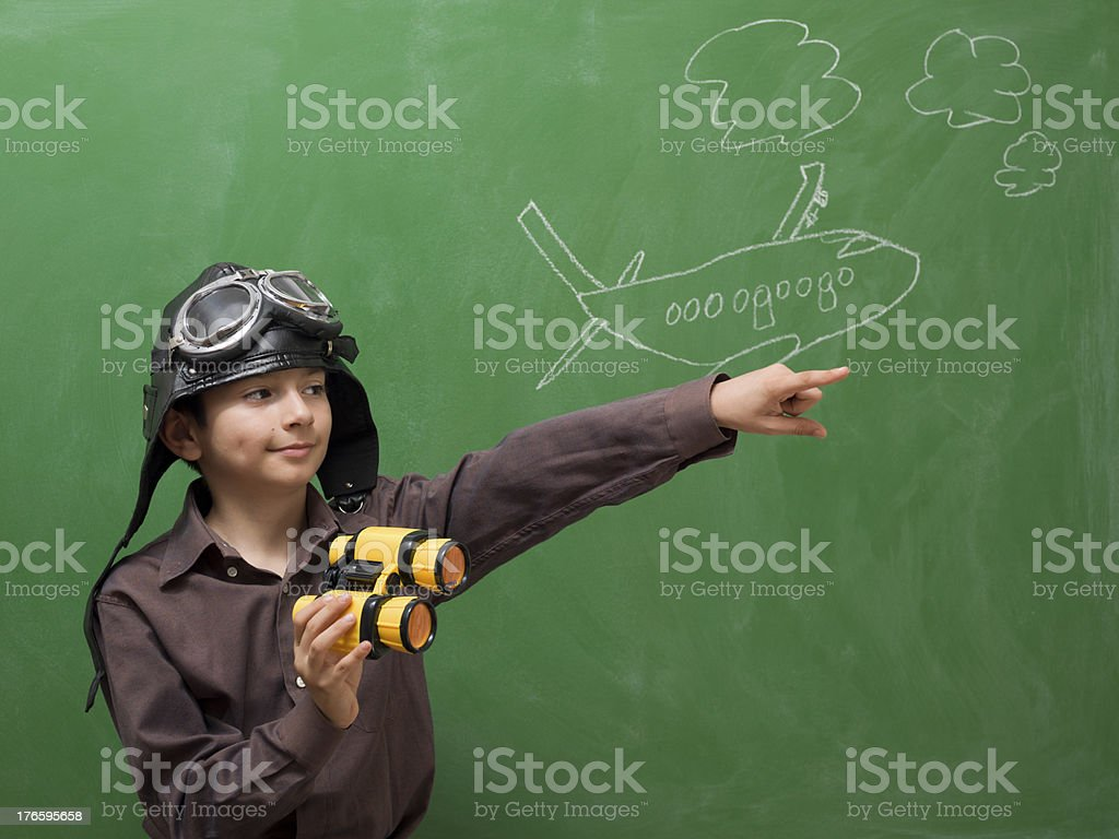 Little boy with flying goggles holding binoculars and pointing forward stock photo