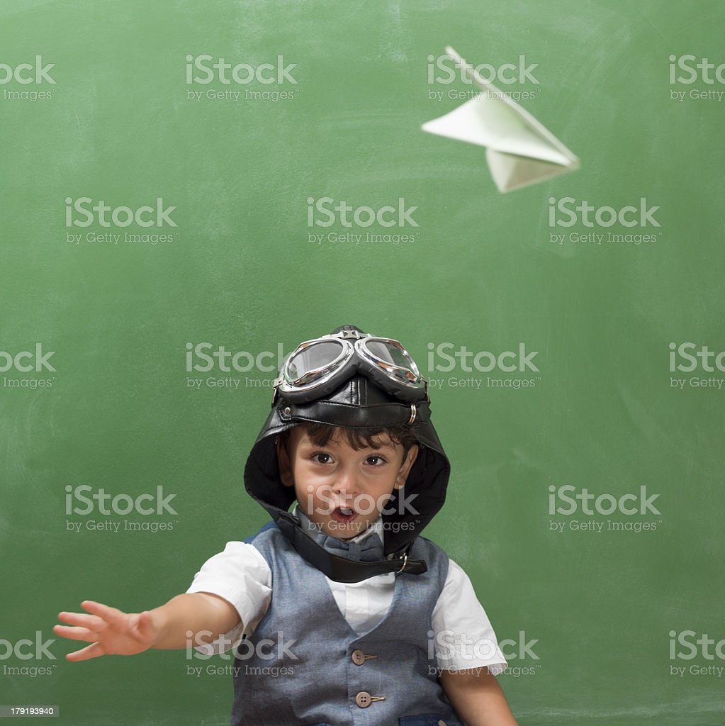 Little boy with flying goggles throwing paper airplane before blackboard stock photo
