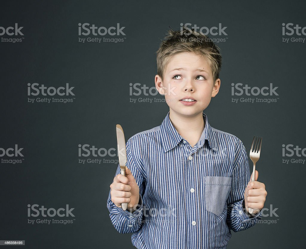 Little boy with fork and knife. Hungry child. stock photo