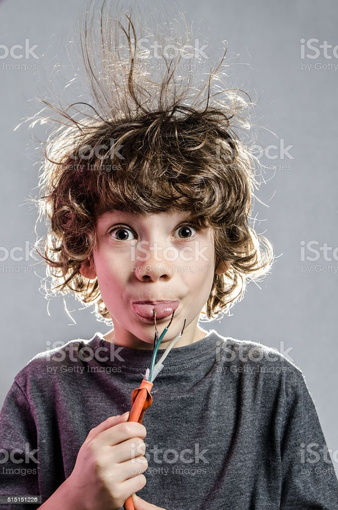Little boy with hair electrified with tongue on wires stock photo