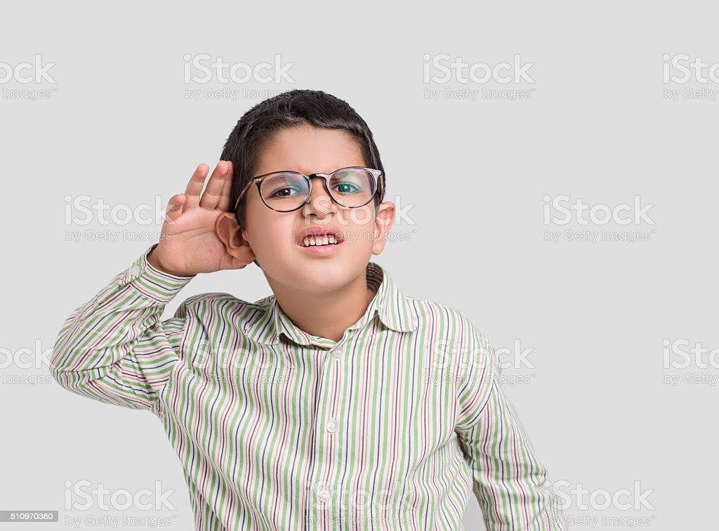 Little boy with hand behind ear listening stock photo