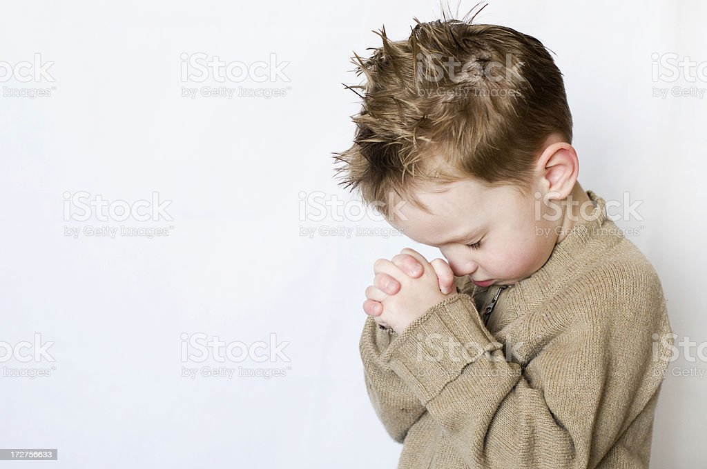 Little boy with hands folded and head bowed in prayer stock photo