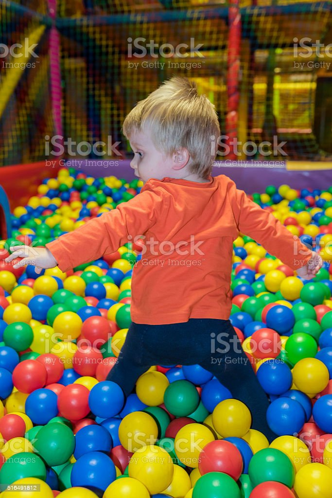 Little boy with hearing aid stands in a ball pool stock photo