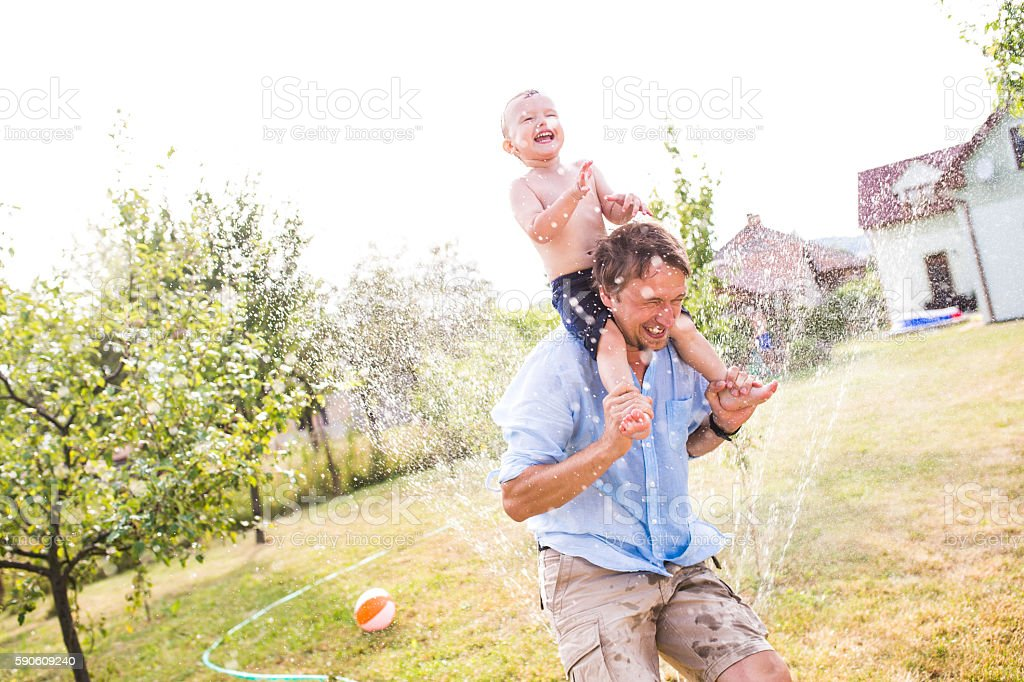Little boy with his father at the sprinkler, summer stock photo