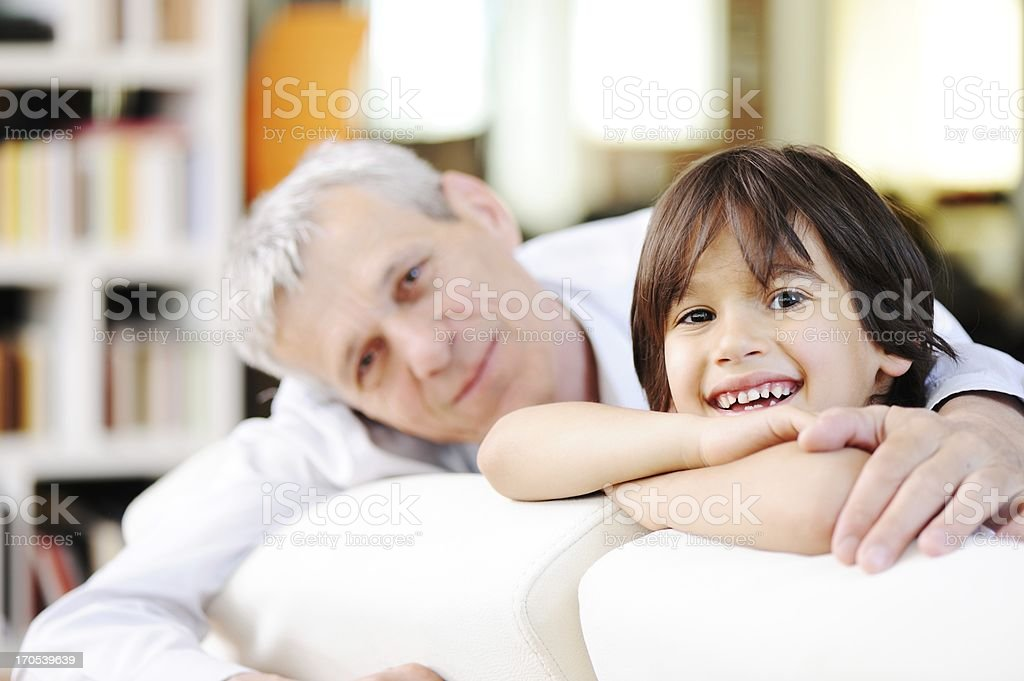 Little boy with his grandfather looking at the camera royalty-free stock photo