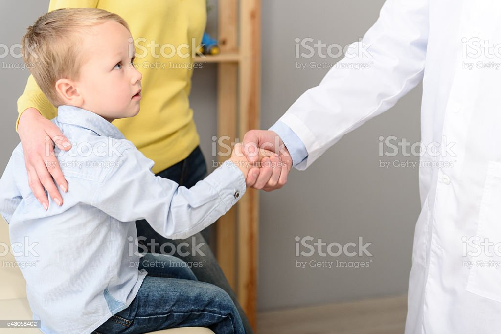 Little boy with his mother at paediatrician on consultation stock photo