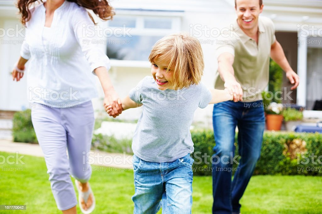 little boy with his parents playing in front of house royalty-free stock photo
