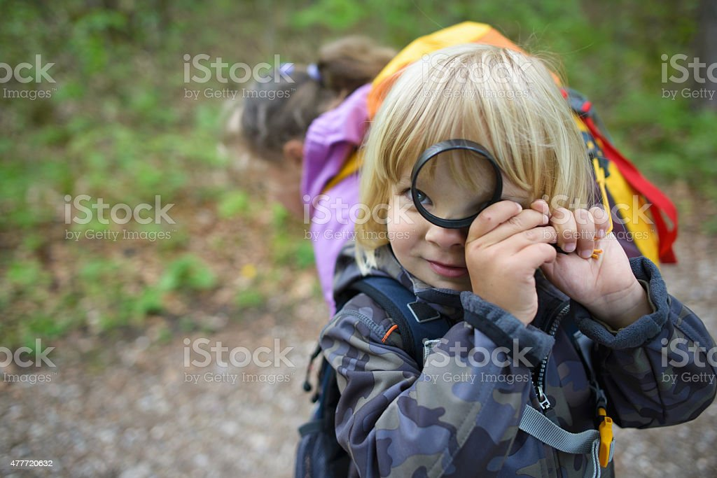 Little boy with magnifying glass in the forest stock photo