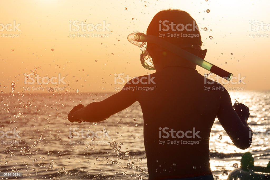little boy with mask and snorkel before sea sunset stock photo