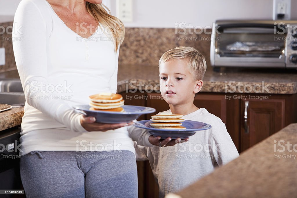 Little boy with mom carrying pancakes stock photo