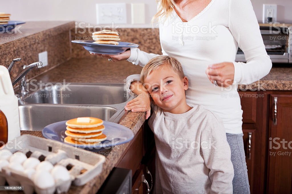 Little boy with mom making pancakes for breakfast stock photo
