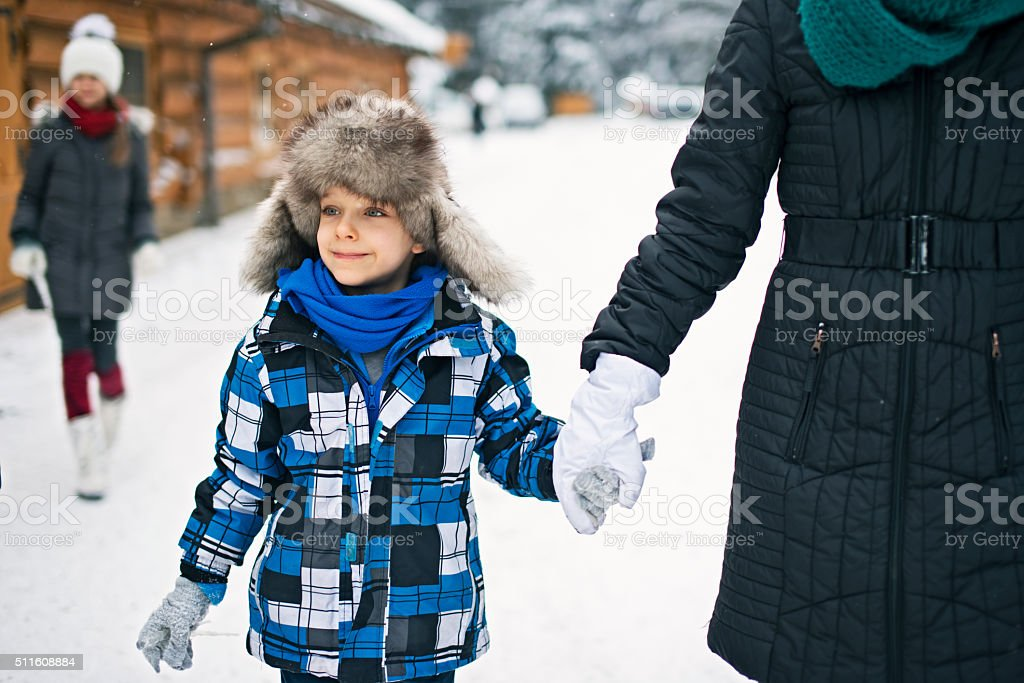Little boy with mother and sister on winter walk stock photo