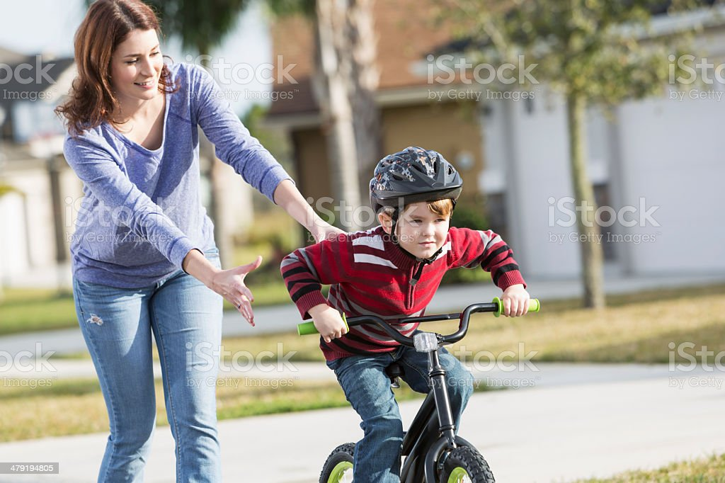 Little boy with mother, learning to ride a bicycle stock photo
