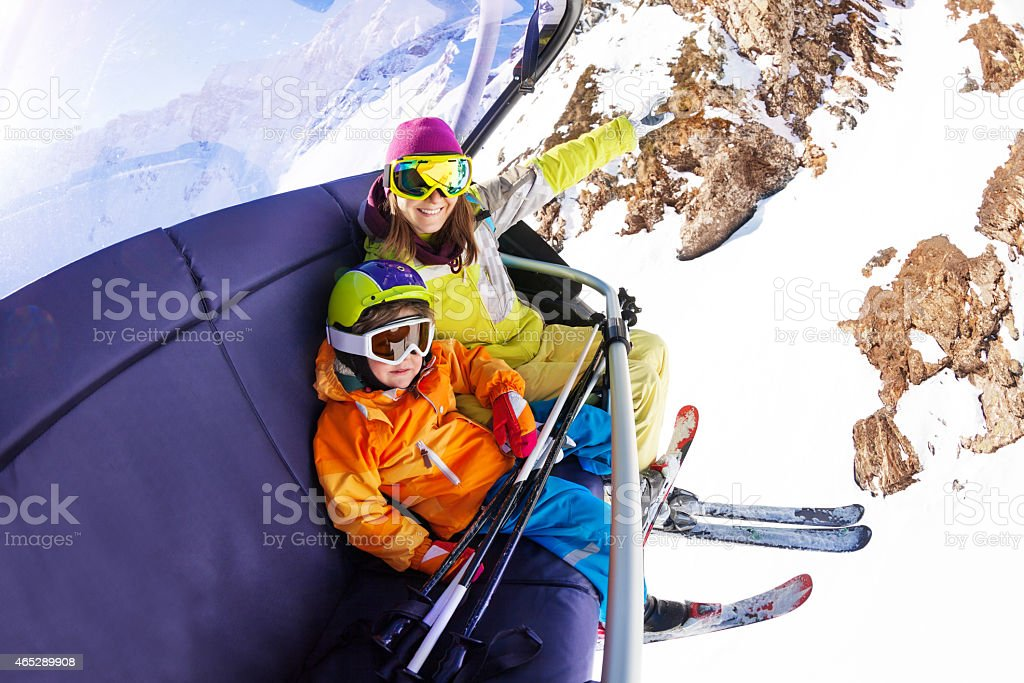 Little boy with mother on ski chair lift stock photo