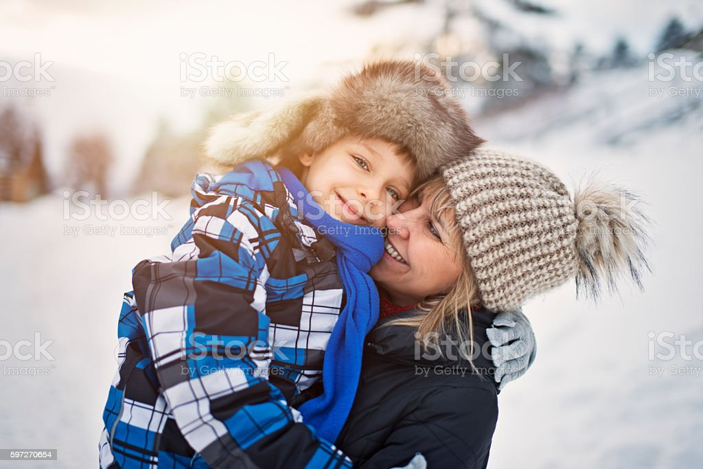 Little boy with mother on winter walk stock photo
