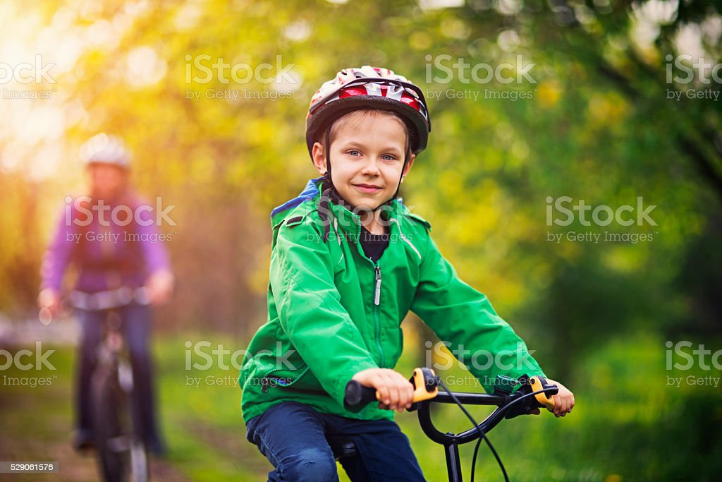 Little boy with mother riding bicycles in beautiful nature stock photo