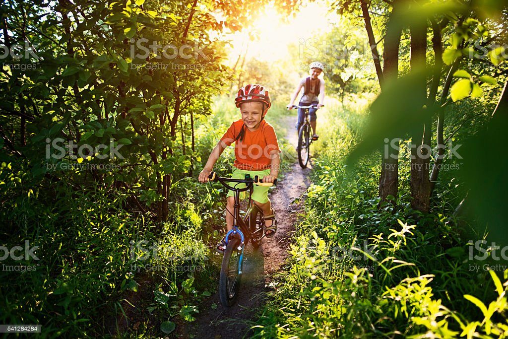 Little boy with mother riding bicycles on beautiful forest path stock photo