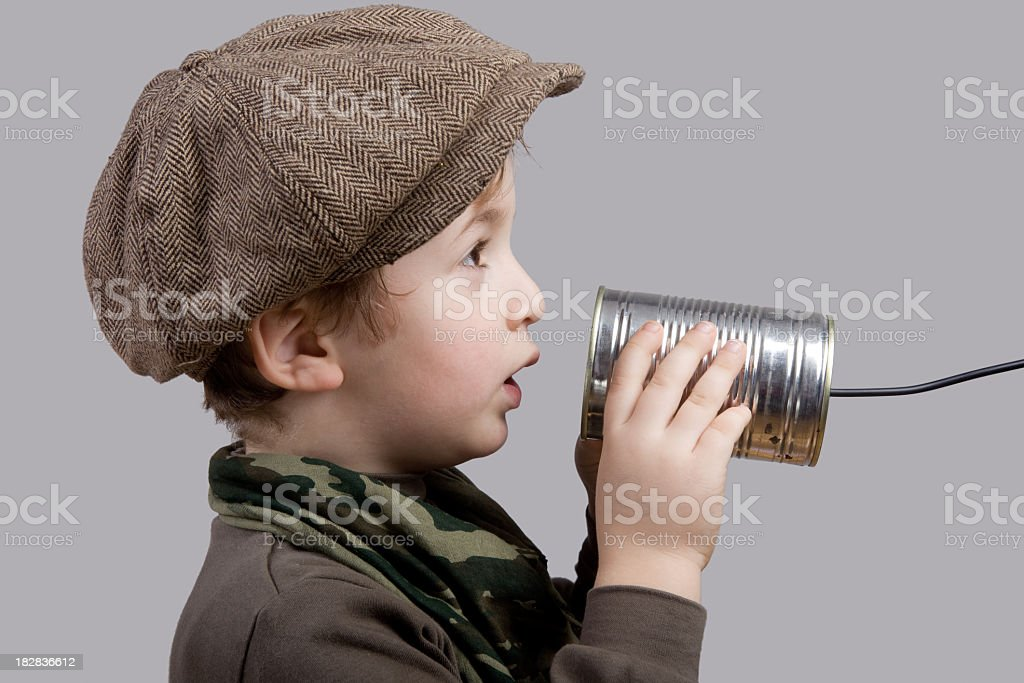 Little Boy With Newsboy Cap Communicating On Tin Can Phone stock photo