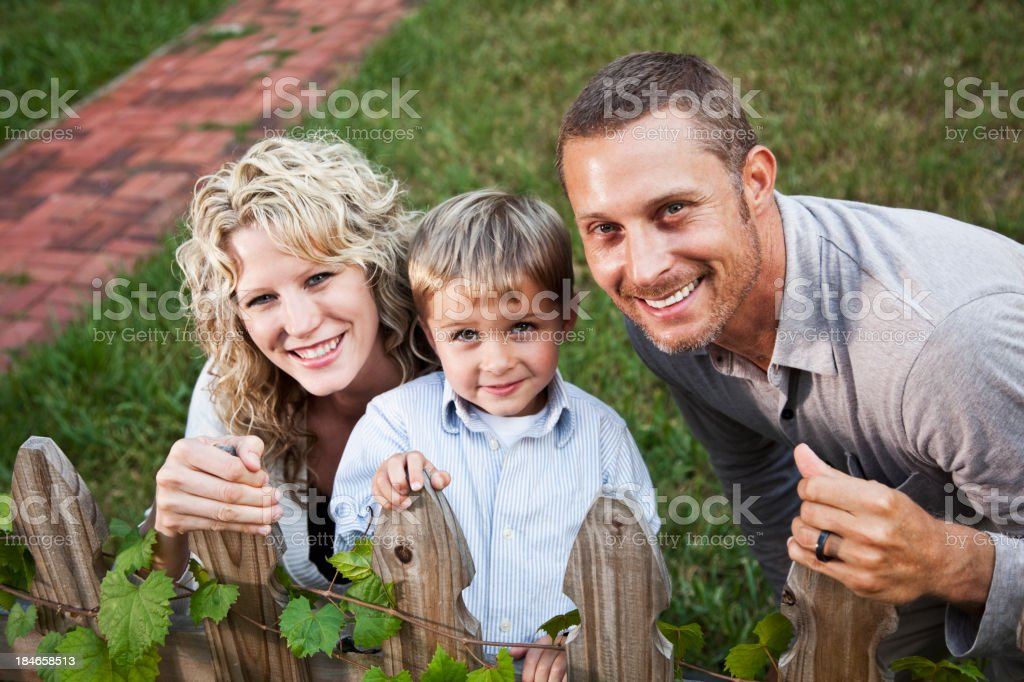 Little boy with parents in backyard stock photo