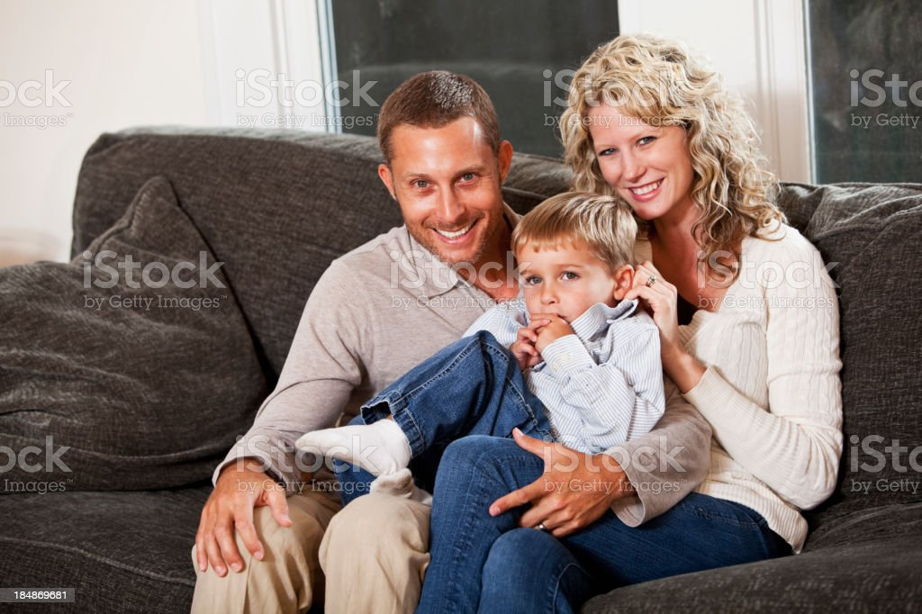 Little boy with parents sitting together on couch royalty-free stock photo