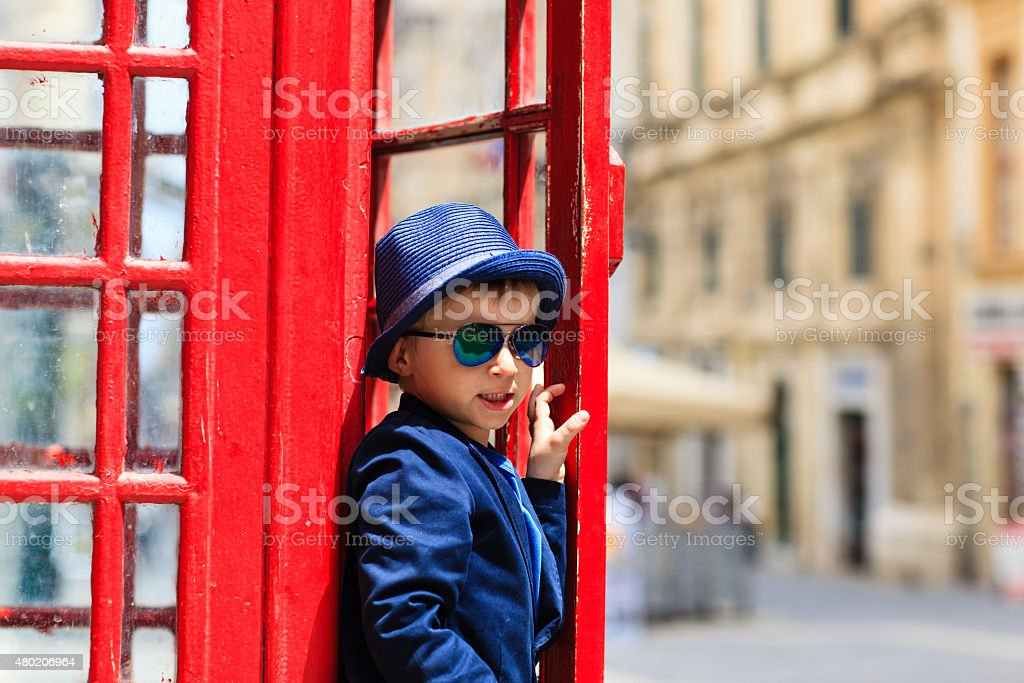 little boy with red telephone box in the city stock photo
