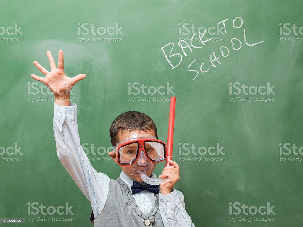 Little boy with snorkel in front of blackboard stock photo
