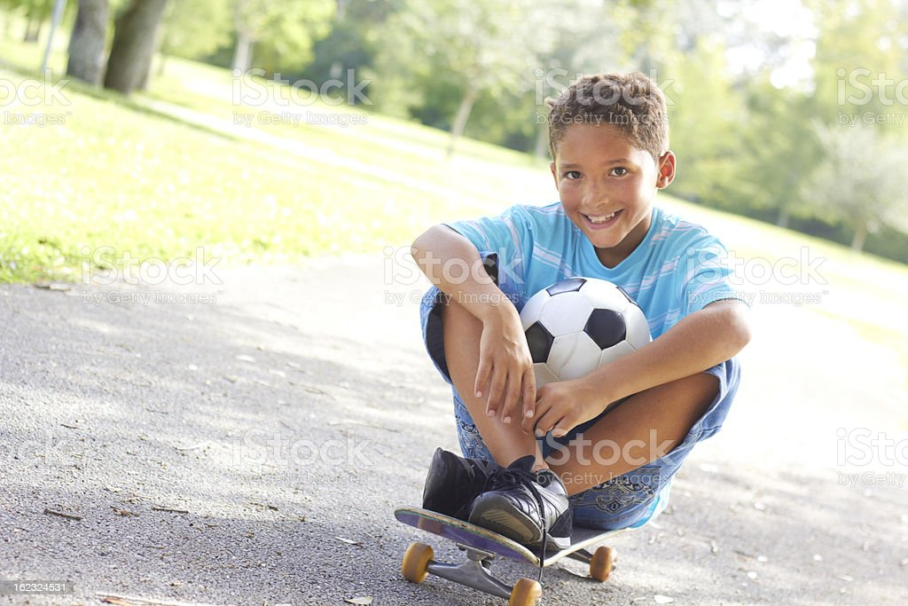 Little boy With Soccer Ball Sitting On Skateboard royalty-free stock photo