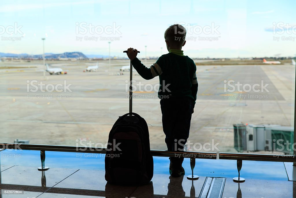 little boy with suitcase waiting in the airport stock photo