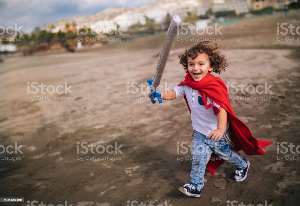 Little boy with sword and cape running on the beach stock photo