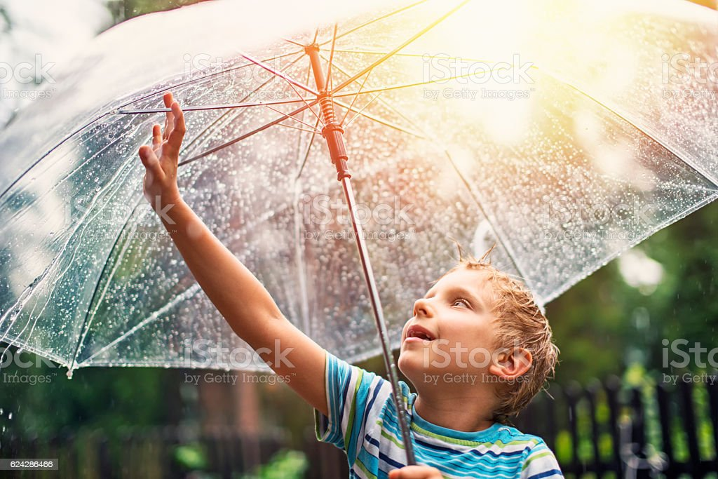 Little boy with transparent umbrella enjoying rain. stock photo